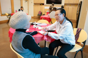 volunteer helping resident with health check up
