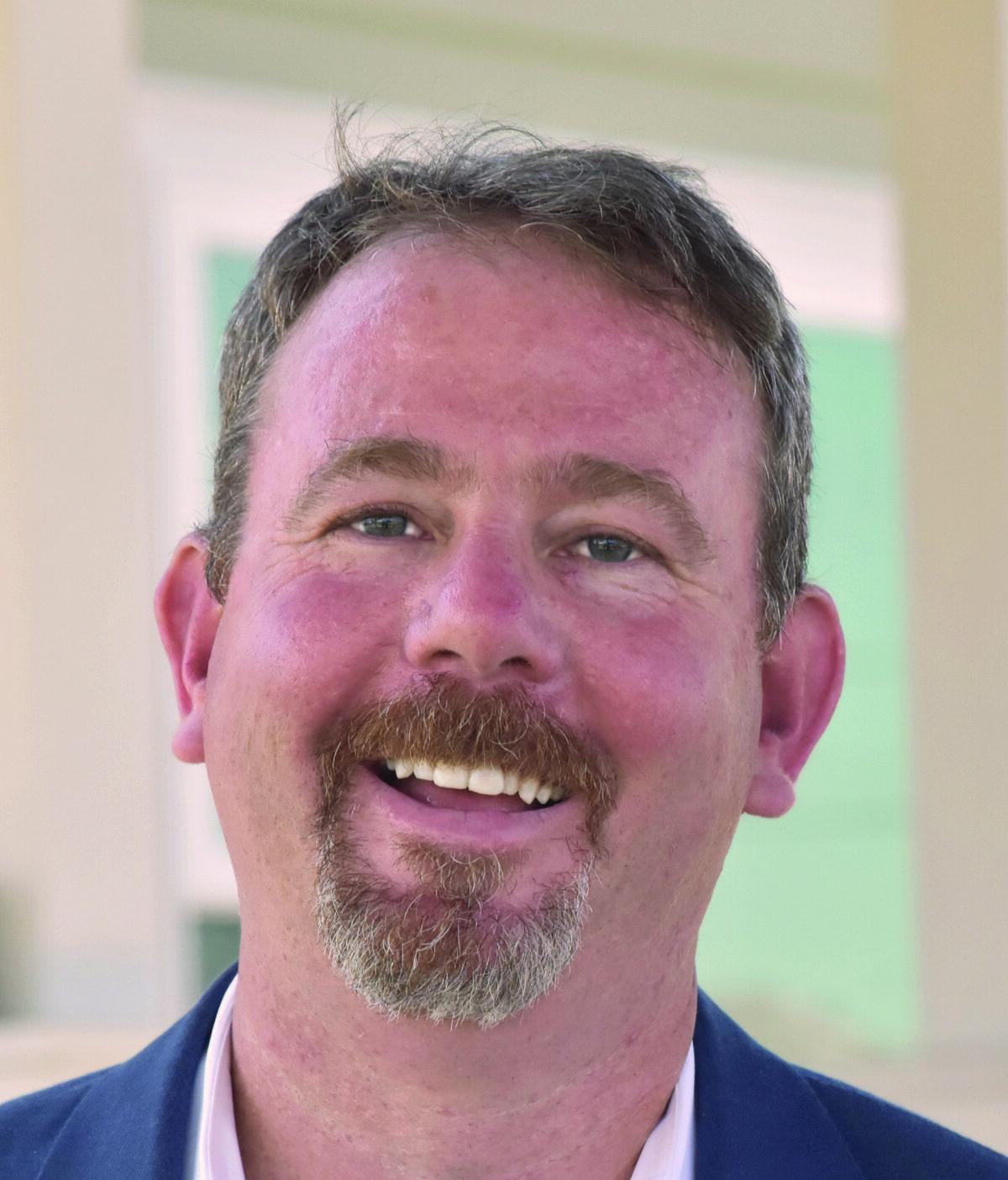 Headshot of Doug Shoemaker, Male Wearing Pink Shirt and Blue Blazer