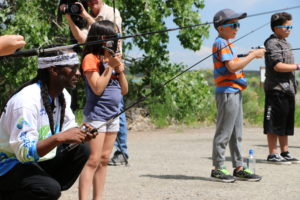 Malik teaching Mercy Housing kids to fish with rod and reel