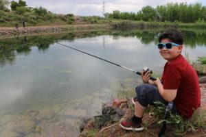 kid fishing and smiling at lake