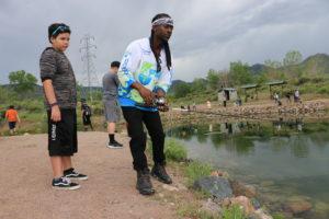 fishing instructor malik with kid at pond