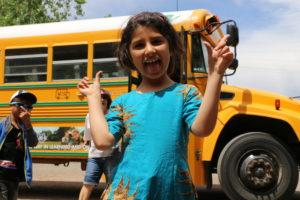 happy child waving in front of school bus