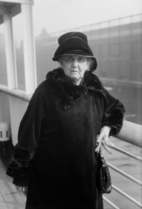 black and white photo of Jane Addams leaning against a railing with a city-scape in the background