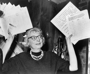 black and white photo of Jane Jacobs holding papers in the air triumphantly while wearing her famed glasses and pearls