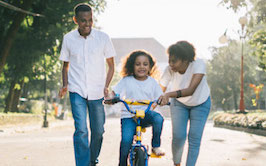 family with child on bike