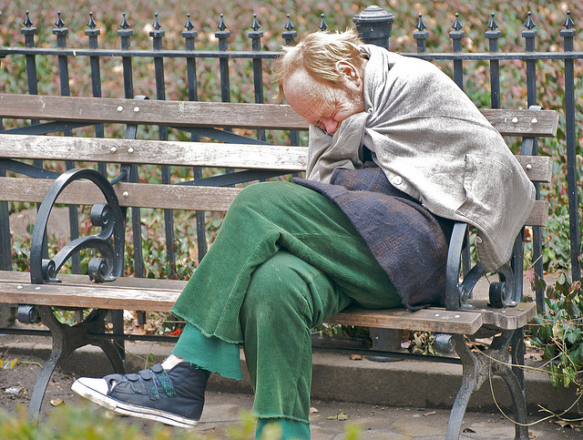 man experiencing homelessness on a bench