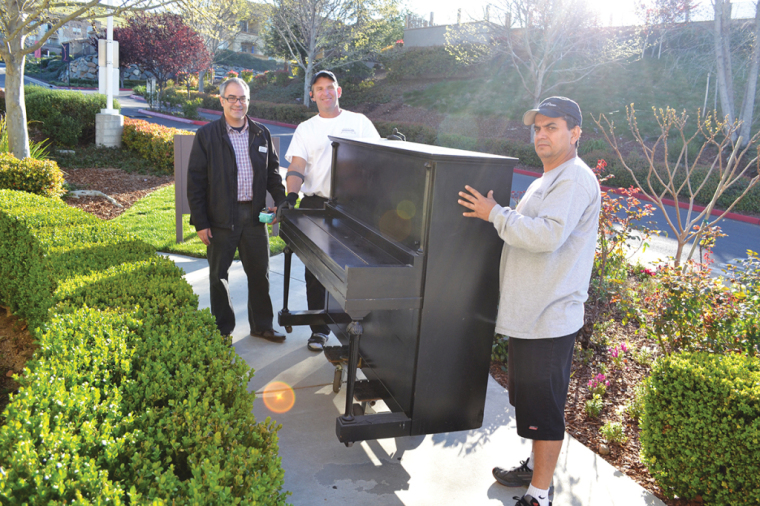 Eddie Zacapa, left, leads the way for Steve Stokes and his employee to deliver a donated piano to White Rock Village
