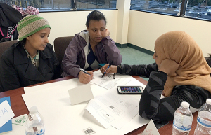 Community Health Promoter Kedija Hashim (R) trains Lichi and Selamawit, two resident leaders from Windsor Heights, on event planning.
