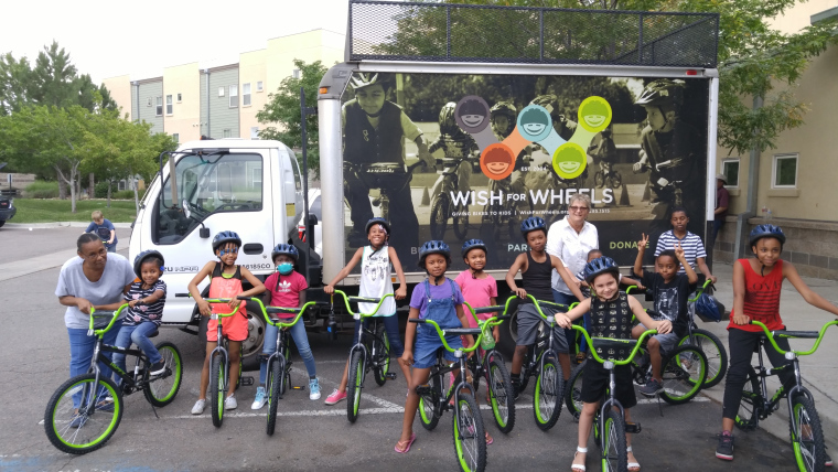 A picture of a group of children with new, green-colored bikes