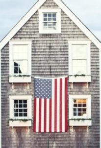 american flag draped across house