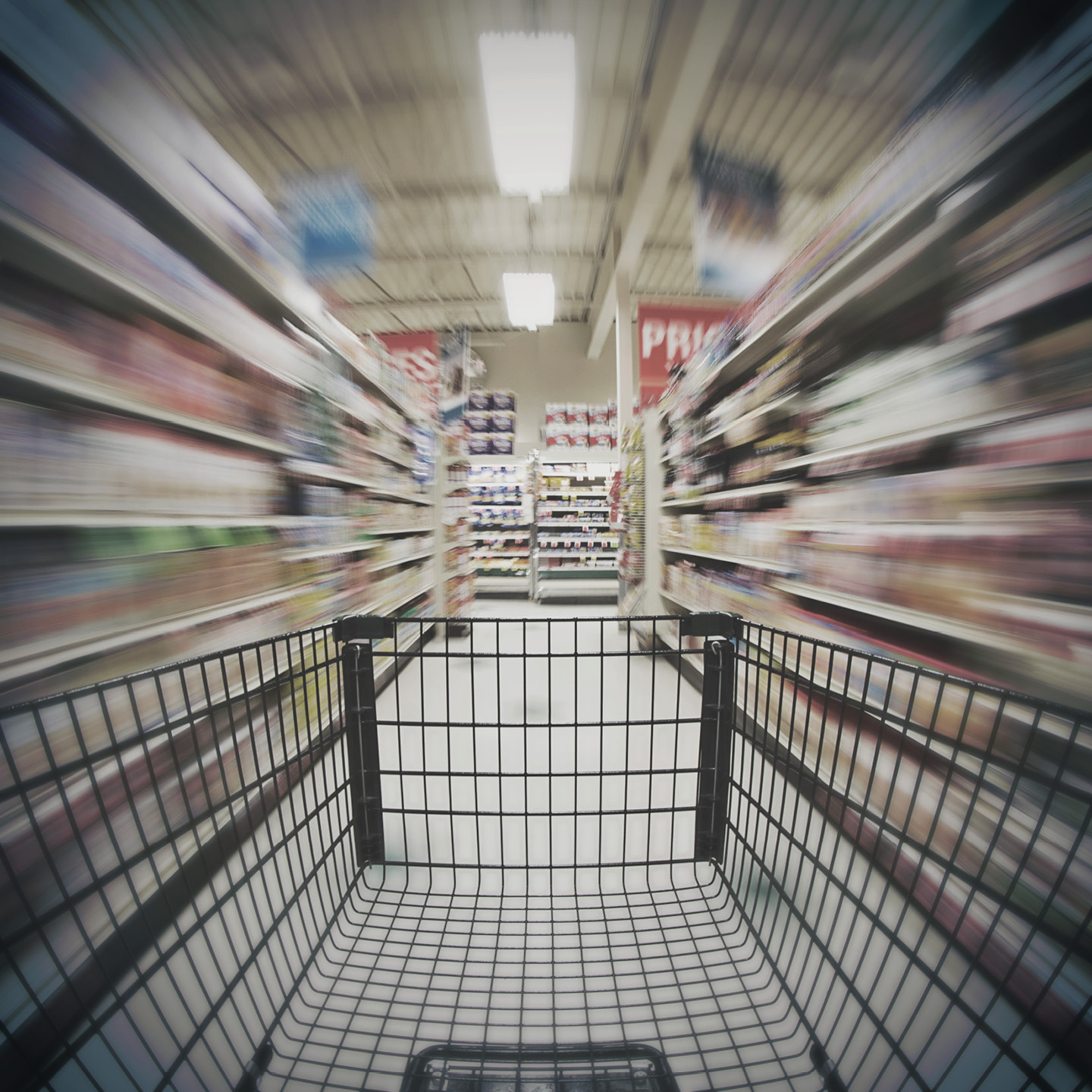 An empty shopping cart being pushed down a grocery store aisle