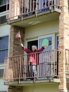 A senior woman waves an American flag from her balcony