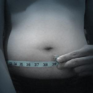 A person measuring their waistline