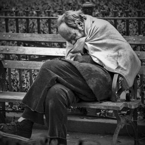 Man sitting on park bench trying to get warm, with photo credit to Flickr user Ed Yourdon