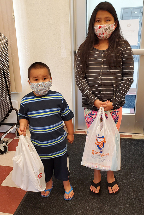 A brother and sister holding bags of school supplies